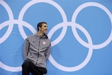 United States' Michael Phelps smiles on the podium before being presented with the gold medal in the men's 100-meter butterfly swimming final at the Aquatics Centre in the Olympic Park during the 2012 Summer Olympics in London, Friday, Aug. 3, 2012. (AP Photo/Michael Sohn)