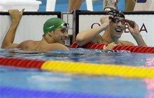 United States' Michael Phelps, right, and South Africa's Chad le Clos react to their scores in the men's 100-meter butterfly swimming final  at the Aquatics Centre in the Olympic Park during the 2012 Summer Olympics in London, Friday, Aug. 3, 2012. Phelps won a gold medal in the event, le Clos won a silver medal. (AP Photo/Michael Sohn)