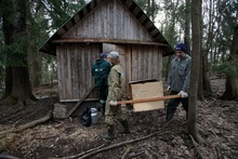 ADVANCE FOR USE SUNDAY, AUG. 5, 2012 AND THEREAFTER - In this Friday, April 20, 2012 photo, from left, Vasily Pazhetnov, Elena Zharkova and Sergey Pazhetnov transport a box with bear cubs and supplies into a