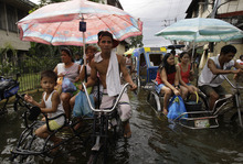 Residents ride a pedicab along a flooded street in Valenzuela city, north of Manila, Philippines on Tuesday July 31, 2012. Typhoon Saola dumped torrents of rain as it swept past the Philippines, killing at least seven people and displacing more than 20,000 others by Tuesday. (AP Photo/Aaron Favila)