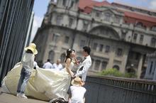 A newly wed couple poses for wedding photo shooting in Shanghai, China, Tuesday July 31, 2012. (AP Photo/Eugene Hoshiko)
