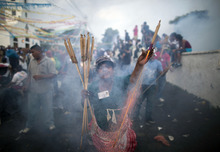 A woman launches a firework during Santo Domingo de Guzman celebrations in Managua, Nicaragua, Wednesday, Aug 1, 2012. The first 10 days of August are reserved for the carnival-like celebrations honoring the capital's city patron saint, Santo Domingo de Guzman, with processions, bullfights, parties and church services. (AP Photo/Esteban Felix)