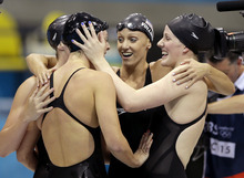 United States' Shannon Vreeland, left, and Missy Franklin, right, embrace Allison Schmitt, foreground, and Dana Vollmer, center, after they won gold in the women's 4x200-meter freestyle relay swimming final at the Aquatics Centre in the Olympic Park during the 2012 Summer Olympics in London, Wednesday, Aug. 1, 2012. (AP Photo/Matt Slocum)