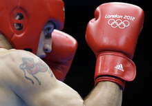 Azerbaijan's Teymur Mammadov (in red) fights Australia's Jai Tapu Opetaia during a heavyweight 91-kg preliminary boxing match at the 2012 Summer Olympics, Wednesday, Aug. 1, 2012, in London. (AP Photo/Patrick Semansky)