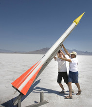 Paul Fraughton | Salt Lake Tribune Tobin Yehle, 19, and his father, Jim Yehle, right, push their rocket into position on the launching pad at the Utah Rocket Club's Hellfire 2012, an annual rocket launch  held on the Bonneville Salt Flats near Wendover.  Friday, August 3, 2012