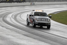 A safety truck drives around the track as the NASCAR Sprint Cup Series auto race was postponed due to rain, Sunday, Aug. 5, 2012, at Pocono Raceway in Long Pond, Pa. (AP Photo/Mel Evans)