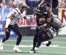 PNI0805-spt rattlers  073012419tk   --  8/4/12- Utah Blaze defenders Will Mulder, left, and Al Phillips (CQ), right, tackle Arizona Rattlers WR Kerry Reed (CQ) during the first quarter of Saturday's playoff game at U.S. Airways Center. Pat Shannahan/The Arizona Republic