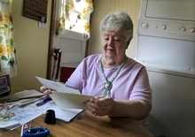 In this July 26, 2012, photo, Neta Homier looks over bills in her home in Toledo, Ohio. Homier says she relies on Social Security to pay her bills and while she is confident the program will continue to help her she fears it will not be able to rely on it.