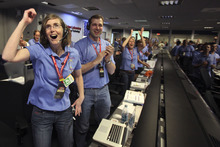 Kelley Clarke, left, celebrates as the first pictures appear on screen after a successful landing inside the Spaceflight Operations Facility for NASA's Mars Science Laboratory Curiosity rover at Jet Propulsion Laboratory  in Pasadena, Calif.,  Sunday Aug. 5, 2012. The Curiosity robot is equipped with a nuclear-powered lab capable of vaporizing rocks and ingesting soil, measuring habitability, and potentially paving the way for human exploration. (AP Photo/Brian van der Brug, Pool)