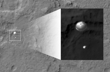 In this image released by NASA/JPL-Caltech/Univ. of Arizona, NASA's Curiosity rover and its parachute, left, descend to the Martian surface on Sunday, Aug. 5, 2012. The high-resolution Imaging Science Experiment (HiRISE) camera captured this image of Curiosity while the orbiter was listening to transmissions from the rover. The inset image is a cutout of the rover stretched to avoid saturation. The rover is descending toward the etched plains just north of the sand dunes that fringe