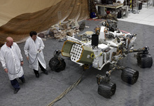 Engineers work on a model of the Mars rover Curiosity at the Spacecraft Assembly Facility at NASA's Jet Propulsion Laboratory in Pasadena, Calif., Thursday, Aug. 2, 2012. After traveling 8 1/2 months and 352 million miles, Curiosity will attempt a landing on Mars the night of Aug. 5, 2012. (AP Photo/Damian Dovarganes)