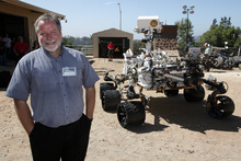 In this July 25, 2012 photo, Rob Manning, chief engineer, speaks to media at NASA Mars Yard at NASA's Jet Propulsion Laboratory in Pasadena. Beside Manning is a model of the Mars rover, Curiosity. After traveling 8 1/2 months and 352 million miles, Curiosity landed on Mars Sunday night. (AP Photo/Nick Ut)