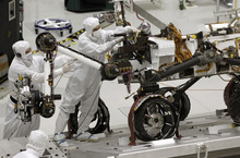 FILE - This Sept. 16, 2010, file photo shows engineers working on the Mars rover Curiosity at NASA's Jet Propulsion Laboratory in Pasadena, Calif. After traveling 8 1/2 months and 352 million miles, Curiosity landed on Mars Sunday night. (AP Photo/Jae C. Hong, file)