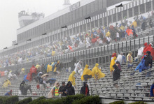 Fans leave the stands after the start of the NASCAR Sprint Cup Series auto race was postponed due to rain on Sunday, Aug. 5, 2012, at Pocono Raceway in Long Pond, Pa. (AP Photo/Mel Evans)