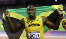 Jamaica's Usain Bolt holds his national flag following his win in the men's 100-meter final during the athletics in the Olympic Stadium at the 2012 Summer Olympics, London, Sunday, Aug. 5, 2012.(AP Photo/Kirsty Wigglesworth)
