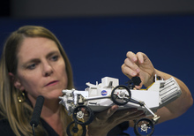 Jennifer Trosper, Mars Science Laboratory, MSL mission manager, JPL, adjusts the high-gain antenna on a rover model during a news briefing on the last data and imagery from Sol 1 at NASA's Jet Propulsion Laboratory in Pasadena, Calif., Monday, August 6, 2012. The rover's primary mission today will be raising its high-gain antenna, which will enable better communication with JPL scientists. (AP Photo/Damian Dovarganes)