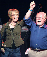 Former congresswoman Gabrielle Giffords joins hands with her former aide Ron Barber on stage as she supports him during a get-out-the-vote rally at the Rialto Theater in downtown Tucson, Ariz., Saturday, June 9, 2012. Voters are deciding in Tuesday's special election whether Republican Jesse Kelly, who narrowly lost to Giffords in 2010, or Democrat Ron Barber, asked by the lawmaker to pursue the seat, will complete the remainder of her term. Giffords relinquished the seat in January to concentrate on her recovery from a gunshot wound to the head. (AP Photo/Arizona Daily Star, Mamta Popat)