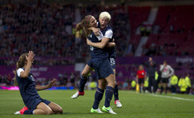 United States' Megan Rapinoe, right, celebrates with teammate Alex Morgan as Tobin Heath slides in on her knees after scoring against Canada during their semifinal women's soccer match at the 2012 London Summer Olympics, Monday, Aug. 6, 2012, at Old Trafford Stadium in Manchester, England. (AP Photo/Jon Super)