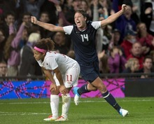 Canada midfielder Desiree Scott (11) bends to her knees as USA forward Abby Wambach (14) celebrates the USA's game winning extra time goal in women's soccer action at the Olympic Games in London on Monday Aug. 6, 2012.  (AP Photo/The Canadian Press, Frank Gunn)