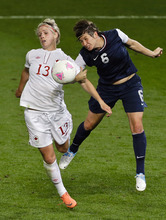 United States' Amy Le Peilbet, right, and Canada's Sophie Schmidt, left, compete for the ball during the semi-final women's soccer match between the USA and Canada in the 2012 Summer Olympics, Monday, Aug. 6, 2012, at Old Trafford in Manchester, England. (AP Photo/Ben Curtis)