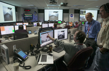 Justin Maki, Mars Science Laboratory Imaging Scientist, JPL, left, and Jordan Evans Engineering Development and Operations Manager, MSL JPL, look at image sets from NASA's Curiosity rover and Mars Reconnaissance Orbiter as they continuing to develop the story of Curiosity's landing on Mars at the Surface Mission Support Area, SMSA NASA's JPL in Pasadena, Calif., Thursday, August 9, 2012. The images from Curiosity's just-activated navigation cameras, or Navcams. (AP Photo/Damian Dovarganes)