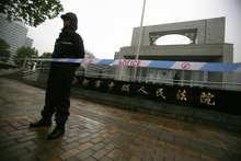 Police officers stand guard at the Hefei City Intermediate People's Court where the murder trial of Gu Kailai, wife of ousted Chinese politician Bo Xilai, takes place Thursday, Aug. 9, 2012 in Hefei, Anhui Province, China. Gu stood trial Thursday for the murder of a British former associate in a tightly orchestrated proceeding that marks a key step to resolving the messiest scandal the leadership has faced in two decades. (AP Photo/Eugene Hoshiko)