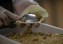 Kim Raff | The Salt Lake Tribune Ana Valdemoros wraps beef empanadas in the kitchen of Martin's Fine Desserts in Salt Lake City on August 3, 2012.