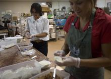 Kim Raff | The Salt Lake Tribune Nichelle Jesen wraps empanadas in the kitchen of Martin's Fine Desserts in Salt Lake City, Utah on August 3, 2012.