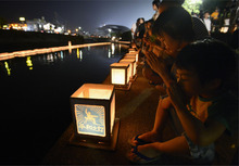 A woman and a boy pray next to lanterns along a river, paying tribute to the victims of the atomic bombing in Nagasaki, southern Japan, Thursday, Aug. 9, 2012. (AP Photo/Kyodo News)