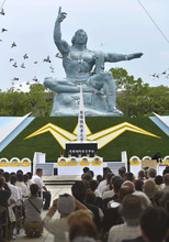 Doves fly over the statue of peace during a memorial ceremony to mark the 67th anniversary of the world's second atomic bomb attack, in Nagasaki, southern Japan, Thursday, Aug. 9, 2012. (AP Photo/Kyodo News)