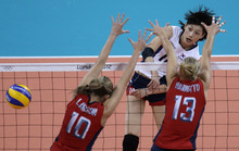 South Korea's Kim Yeon-koung, top, spikes the ball past United States' Jordan Larson and Christa Harmotto (13) during a women's semifinal volleyball match at the 2012 Summer Olympics, Thursday, Aug. 9, 2012, in London. (AP Photo/Jeff Roberson)