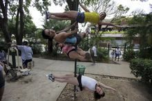 In this photo taken July 1, 2012, from top to bottom, Franceska Garcia, Emerlinda Maglione, Amanda De Pierda and Keryne Este pose for a photo as they practice pole dancing at an outdoor gym during one of their weekend outings to a public park in Caracas, Venezuela.  Pole dancing may have started out in strip clubs, but since the 1990s, it's become an all-ages exercise and sport phenomenon the world over. Now, it's hit the streets in Venezuela, a country that's made beauty and fitness a cult and minted more Miss Universes than any other except the United States. (AP Photo/Fernando Llano)