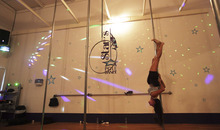 In this photo taken July 11, 2012,  a woman practices pole dancing during a class held in a gym in Caracas, Venezuela. Pole dancing may have started out in strip clubs, but since the 1990s, it's become an all-ages exercise and sport phenomenon the world over. Now, it's hit the streets in Venezuela, a country that's made beauty and fitness a cult and minted more Miss Universes than any other except the United States. (AP Photo/Fernando Llano)