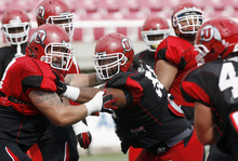 Francisco Kjolseth     The Salt Lake Tribune Sam Brenner, left, and LT Tuipulotu keep an eye on which way the ball is moving as the University of Utah football team gets ready for the season during team practice at Rice-Eccles stadium on Friday, August 10, 2012.