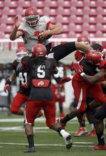 Francisco Kjolseth     The Salt Lake Tribune Quarterback Travis Wilson tries to hurdle himself over the opposition during Utah's scrimmage Friday at Rice-Eccles stadium.