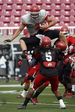 Francisco Kjolseth     The Salt Lake Tribune Quarterback Travis Wilson tries to hurdle himself over the opposition as the University of Utah football team gets ready for the season with a scrimmage game at Rice-Eccles stadium on Friday, August 10, 2012.