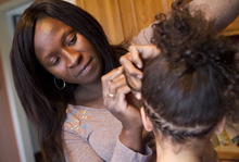Jim Urquhart     The Associated Press Jestina Clayton braids the hair of her daughter, Esther Clayton, 5, at her home Monday, April 25, 2011, in Centerville. Clayton and  the Institute for Justice have filed a federal lawsuit seeking changes to Utah's hair braiding regulations.