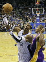 Orlando Magic's Dwight Howard, left, goes up to shoot against Los Angeles Lakers' Andrew Bynum, right, during the first half of an NBA basketball game on Friday, Jan. 20, 2012, in Orlando, Fla. Orlando won 92-80. (AP Photo/John Raoux)