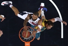 USA's Tyson Chandler slams a dunk against  Australia's David Andersen during a men's quarterfinals basketball game at the 2012 Summer Olympics, Wednesday, Aug. 8, 2012, in London. (AP Photo/Charles Krupa)