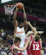 Spain's Serge Ibaka (14) grabs a rebound over Russia's Andrei Kirilenko, left, and Sergey Monya (12) during a men's semifinals basketball game at the 2012 Summer Olympics, Friday, Aug. 10, 2012, in London. (AP Photo/Charles Krupa)