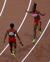 United States' Carmelita Jeter, left, celebrates with teammate Tianna Madison after their win in the women's 4 x 100-meter relay during the athletics in the Olympic Stadium at the 2012 Summer Olympics, London, Friday, Aug. 10, 2012. The United States relay team set a new world record with a time of 40.82 seconds. (AP Photo/Daniel Ochoa De Olza)