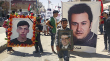 This image made from amateur video released by the Shaam News Network and accessed Saturday, Aug. 11, 2012 purports to show protesters carrying pictures of those killed in anti-government fighting in the predominately Kurdish village of Qamishli, the largest town in Hassake province, Syria, Friday, Aug. 10, 2012. (AP Photo/Shaam News Network via AP video) THE ASSOCIATED PRESS IS UNABLE TO INDEPENDENTLY VERIFY THE AUTHENTICITY, CONTENT, LOCATION OR DATE OF THIS HANDOUT PHOTO