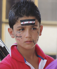 This citizen journalism image released by the Shaam News Network and accessed Saturday, Aug. 11, 2012 purports to show a young protester in the village of Binnish in Idlib province, Syria, Friday, Aug. 10, 2012. Arabic on boy's face reads