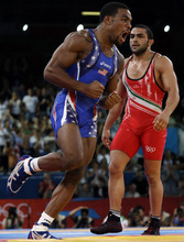 United States' Jordan Ernest Burroughs, in blue, celebrates after winning against Iran's Sadegh Saeed Goudarzi, red, during the gold medal match at a 74-kg men's freestyle wrestling competition at the 2012 Summer Olympics, Friday, Aug. 10, 2012, in London. (AP Photo/Paul Sancya)