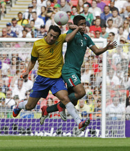 Brazil's Leandro Damiao (9) collides with Mexico's Darvin Chavez (5) during the men's soccer final at the 2012 Summer Olympics, Saturday, Aug. 11, 2012, in London. (AP Photo/Hassan Ammar)