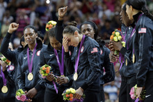 United States' Diana Taurasi, right center, wipes away tear after receiving her gold medal after they defeated France in the  women's gold medal basketball game at the 2012 Summer Olympics, Saturday, Aug. 11, 2012, in London. (AP Photo/Eric Gay)