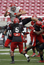 Francisco Kjolseth  |  The Salt Lake Tribune Quarterback Travis Wilson tries to hurdle himself over the opposition during Utah's scrimmage Friday at Rice-Eccles stadium.