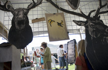 Kim Raff | The Salt Lake Tribune Wooden wall hanging pieces hang in artist Nic Annette Miller's booth as people shop during the 4th annual Craft Lake City Utah's DIY Festival at the Gallivan Center in Salt Lake City, Utah on August 11, 2012.