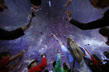Athletes react as confetti rains down on them during the Closing Ceremony at the 2012 Summer Olympics, Monday, Aug. 13, 2012, in London. (AP Photo/Jae C. Hong)