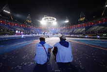 French athletes Amelie Cazae and Julien Bahain sit after the Closing Ceremony at the 2012 Summer Olympics, Monday, Aug. 13, 2012, in London. (AP Photo/Jae C. Hong)